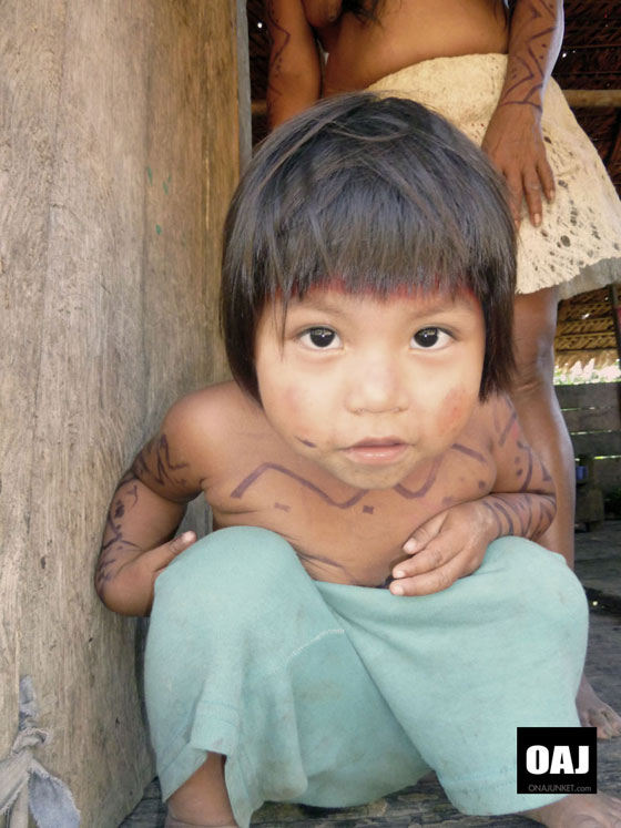 A Huaorani child bends to camera.