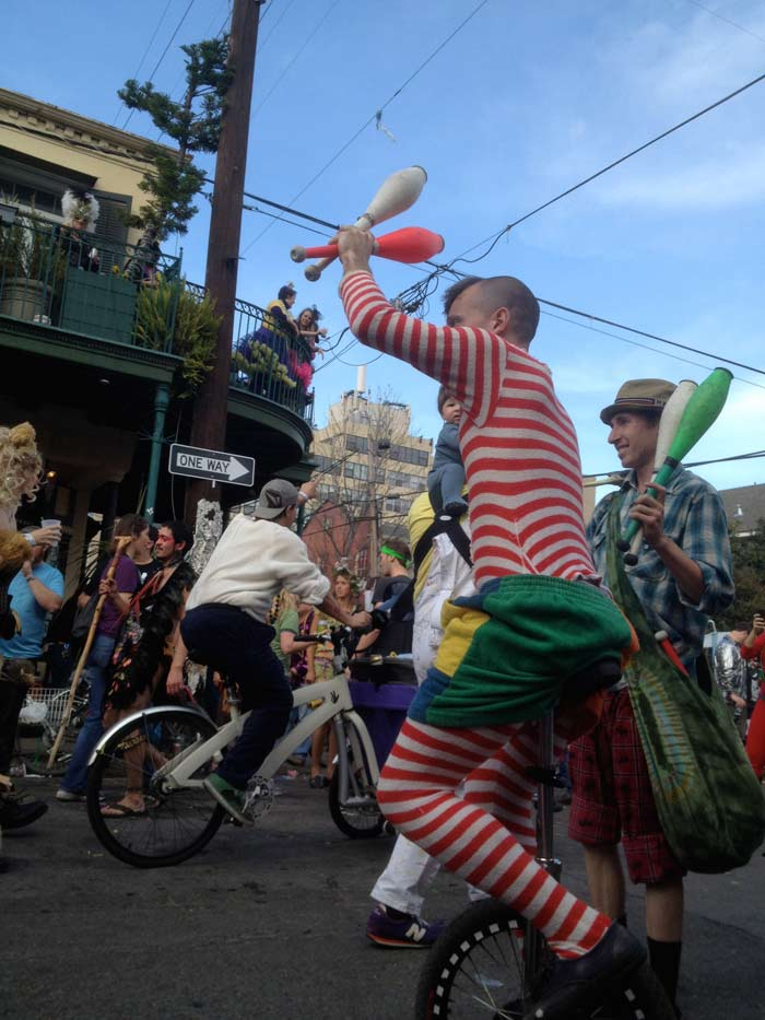 street performers in mardi gras. one man is on a uni-cycle holding up bowling pins. the other behind is following him holding bowling pins as well.