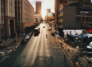 you're looking down a semi-empty street in a city. A bus travels by itself down the street towards between darken buildings. it's heading towards the bottom of the image. the sun rises in the horizon.